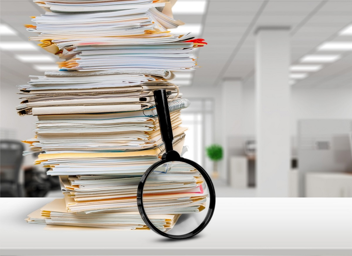Stack of Documents and Magnifying Glass