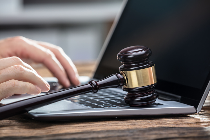 Person Writes Email on Laptop With Gavel